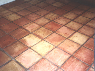 This Gilbert Arizona tile floor is covered in dirt with the grout darkened to a dark brown color before  cleaning